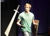 Actor Bradley James shows the audience one of Prince Arthurs favourite sword flourishes (BAFTA / Jonny Birch).
