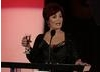 Evening's host Sharon Osbourne take to the stage with drink in hand......