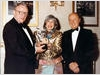 Mitzi Cunliffe is awarded a special version of her BAFTA Mask by Richard Price (l) and Johnny Goodman (r).