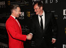 Ceremony host Alan Cumming shakes hands with director Quentin Tarantino.