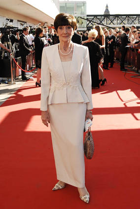 This cream coloured dress and matching jacket is incredibly sophisticated. June is the perfect example of a lady who dresses elegantly for her age. The flare at the bottom of the jacket gives the illusion of hips to June's slim figure, and the tailored pencil skirt shows off her long legs. The cream colour works very well with June complexion, as she has a warm skin tone and dark eyes. Steer clear of cream or very pale pastels if you have very fair colouring, as it can easily wash you out.