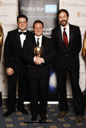 Rowan Joffe (centre) receives the Director Fiction/Entertainment award for The Shooting Of Thomas Hurndall from The IT Crowd star Chris O'Dowd (BAFTA / Richard Kendal).