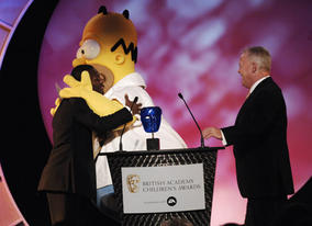 England footballer Shaun Wright-Phillips receives a warm welcome from Homer Simpson, whose movie won the BAFTA Kids' Vote in association with Electronic Arts