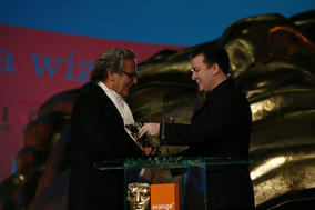 Ricky Gervais (right) presents the BAFTA for Animated Feature Film to George Miller for Happy Feet (BAFTA / Brian Ritchie).
