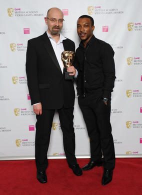 "Actor Ashley Walters with one of the winning team, Christophe Villez. The jury praised the game's ""rousingly captivating worlds populated by beautiful characters with great interactivity."""