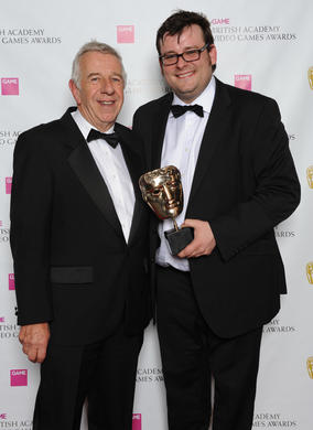 Presenter Geoff Heath OBE and Kevin Flynn of Electronic Arts. The jury described the game as excelling at delivering unprecedented levels of player teamwork and roles in a vast, gripping environment.