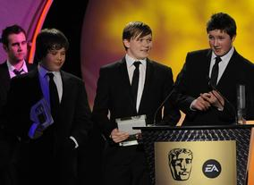Dan Pearce, Sam Taylor and James Cook of Beached Whale Productions take the BYGD award for their game HAMSTER: Accidental World Domination. Pic: BAFTA/Steve Finn
