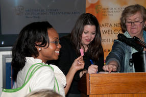 A lucky raffle winner shows her ticket at the Awards party in New York to Jasmine Rinde, event producer and CEO, Christina Thomas